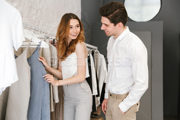 Happy young couple shopping for clothes Stock photo © deandrobot