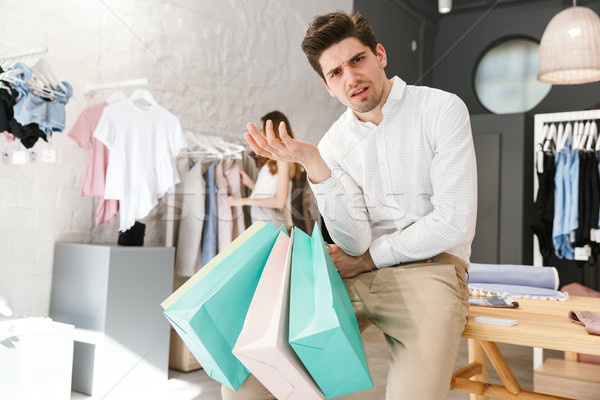 Confused man sitting and holding shopping bags Stock photo © deandrobot