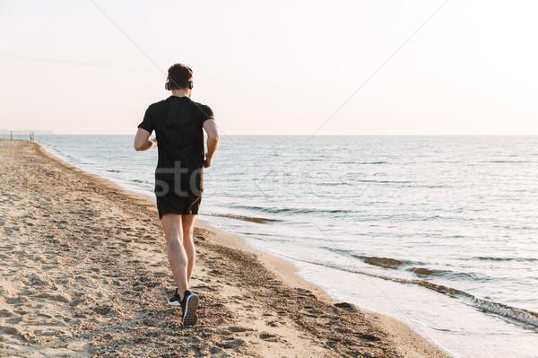 Hátulnézet fiatal sportoló fut tengerpart zenét hallgat Stock fotó © deandrobot