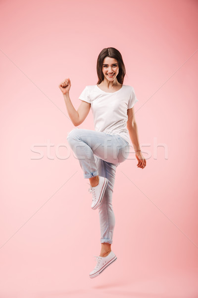 Full length of an excited young woman jumping Stock photo © deandrobot