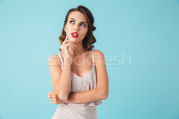 Thoughtful brunette woman in dress touching chin and looking away Stock photo © deandrobot