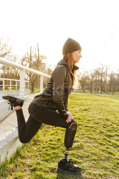 Photo of disabled running woman in sportswear, squatting and str Stock photo © deandrobot