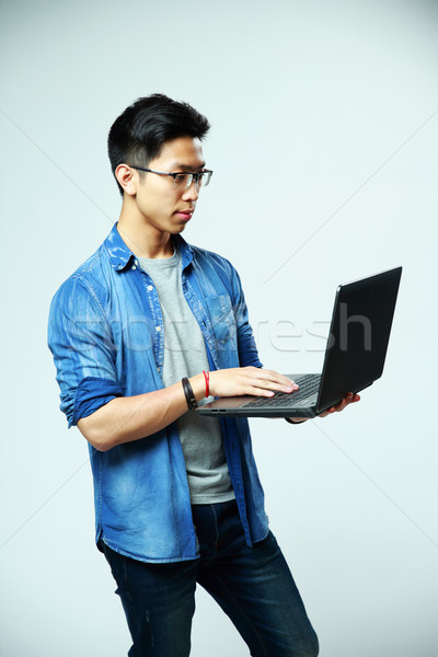 Handsome asian man using laptop on gray background Stock photo © deandrobot