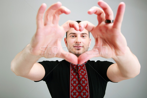 Portrait of a man makes the heart using fingers on gray background Stock photo © deandrobot