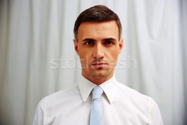 Portrait of a confident businessman in white shirt Stock photo © deandrobot