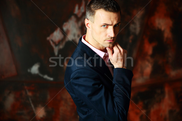 Cool stylish man standing over industrial background Stock photo © deandrobot