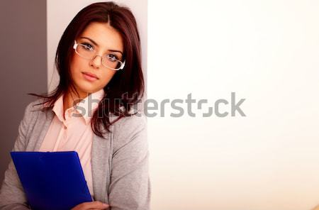 Young businesswoman looking at smartphone on her workplace in office Stock photo © deandrobot