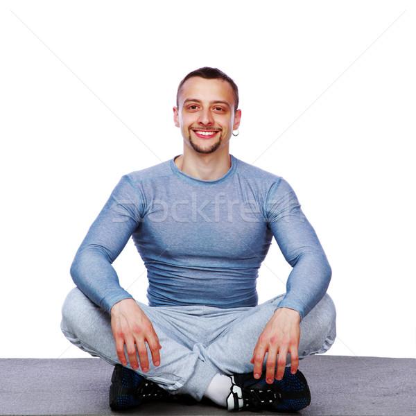 Boldog sportoló ül lótusz pozició fehér Stock fotó © deandrobot