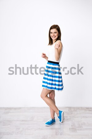 Full length portrait of a happy woman standing with follow me gesure Stock photo © deandrobot