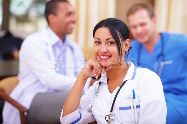 Medical latin doctor woman smiling indoors with her collegues working behind Stock photo © deandrobot