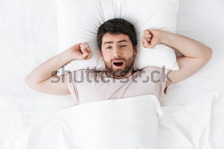 Angry young woman covering her ears with pillows Stock photo © deandrobot