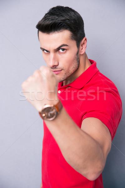 Giovani casuale uomo pugno grigio Foto d'archivio © deandrobot