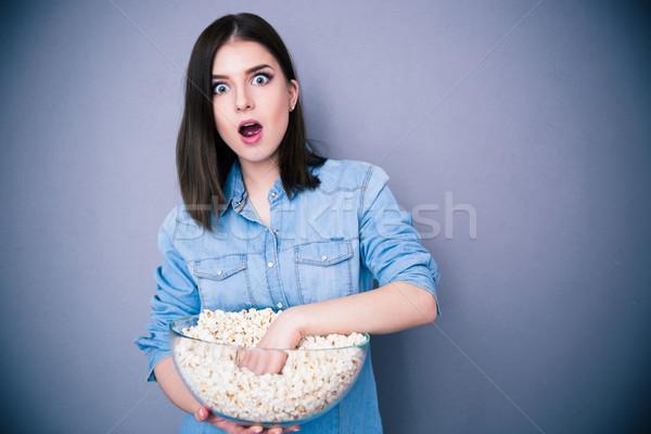 Maravilhado mulher bonita alimentação pipoca cinza olhando Foto stock © deandrobot