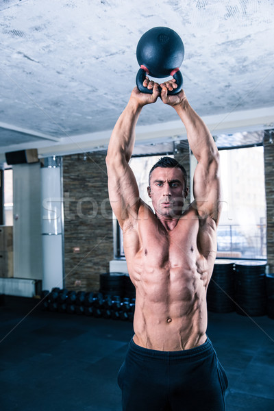Bodybuilder man workout with kettle ball Stock photo © deandrobot