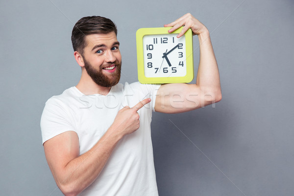 Stock photo: Smiling man pointing finger on wall clock