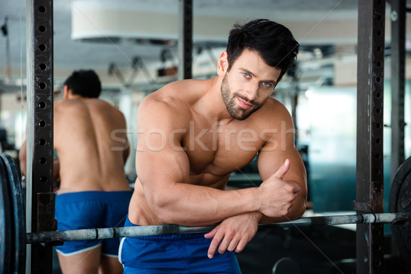 Muscular man showing thumb up in fitness gym Stock photo © deandrobot