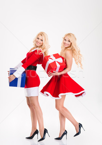 Sisters twins in santa claus costumes dancing with present boxes Stock photo © deandrobot