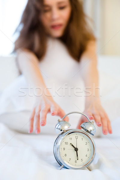 Woman trying to turn off the alarm clock Stock photo © deandrobot