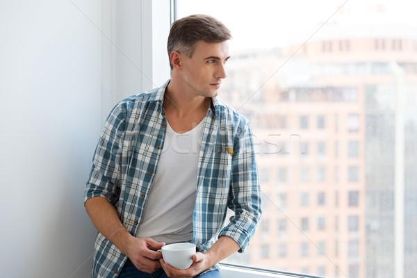 красивый мужчина сидят подоконник питьевой кофе красивый Сток-фото © deandrobot