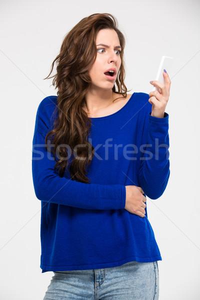 Amazed woman reading message on smartphone Stock photo © deandrobot