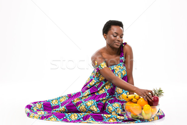 Smiling african american woman sitting with glass bowl of fruits Stock photo © deandrobot