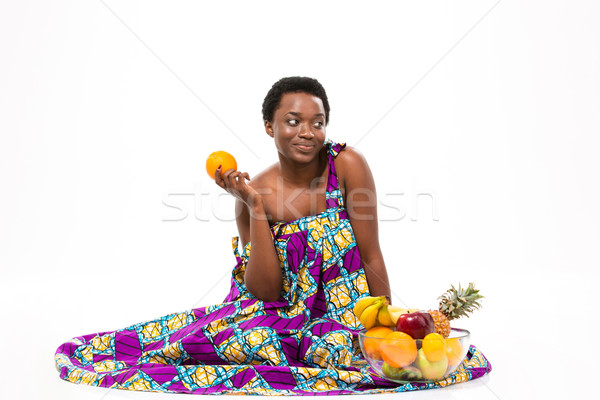 Cute pensive african american woman sitting and holding orange Stock photo © deandrobot