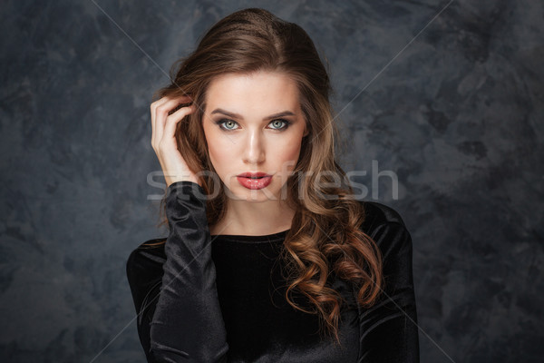 Sensual young woman touching her hair by hand Stock photo © deandrobot