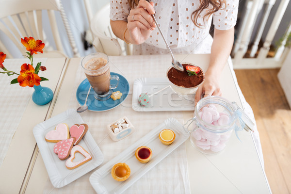 Young woman eating dessert and drinking latte at the table Stock photo © deandrobot