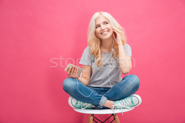 Woman sitting on the chair and listening music in headhpones Stock photo © deandrobot