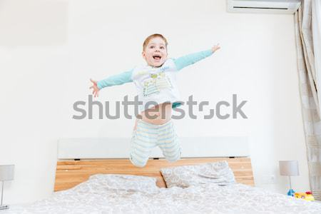 Cheerful little boy showing tongue and jumping on bed Stock photo © deandrobot