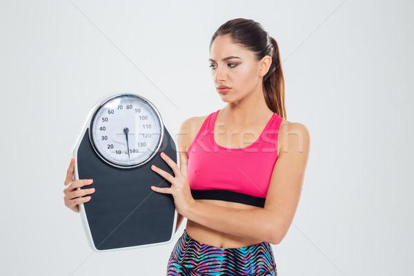 Szomorú fitnessz nő tart gép izolált fehér Stock fotó © deandrobot