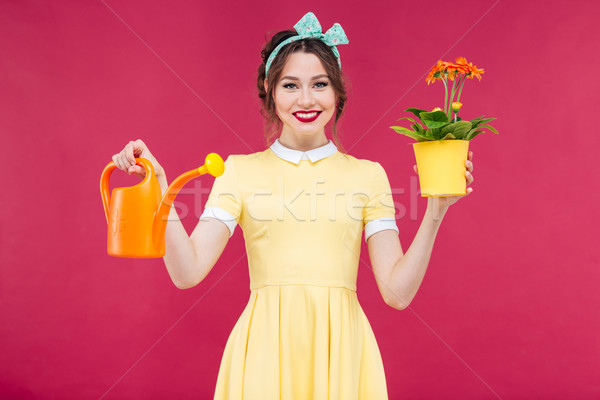 Smiling pinup girl holding flowers in pot and watering can Stock photo © deandrobot