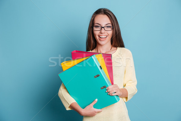 Young happy woman holding colorful binders over blue background Stock photo © deandrobot