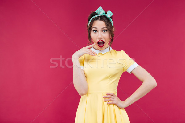 Surprised pinup girl in yellow dress standing with mouth opened Stock photo © deandrobot