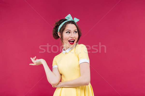 Cheerful playful pinup girl in yellow dress pointing away Stock photo © deandrobot