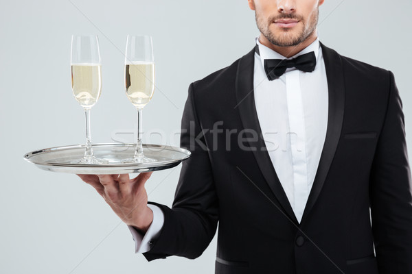 Glasses of champagne on tray holded by waiter in tuxedo Stock photo © deandrobot