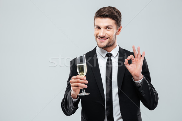 Cheerful young businessman drinking champagne and showing ok sign Stock photo © deandrobot