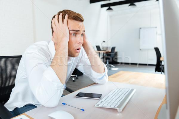 Shocked amazed young businessman using computer Stock photo © deandrobot