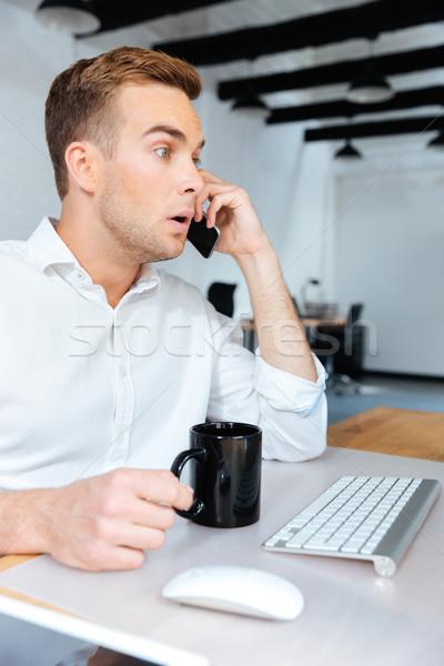Verwonderd verwonderd zakenman praten mobiele telefoon drinken Stockfoto © deandrobot