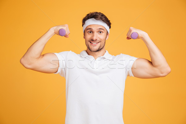 Cheerful young sportsman holding dumbbells and showing biceps Stock photo © deandrobot