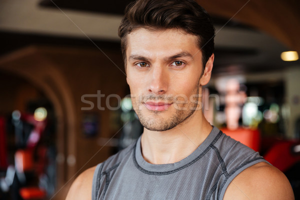 Confident young man athlete in fitness club Stock photo © deandrobot