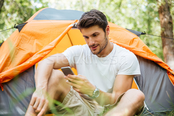 Man tourist using mobile phone in toristic tent at forest Stock photo © deandrobot