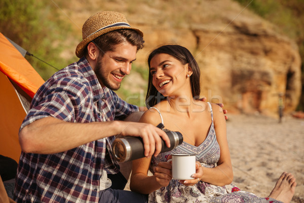 Young couple drinking hot tea at the bonfire while camping Stock photo © deandrobot
