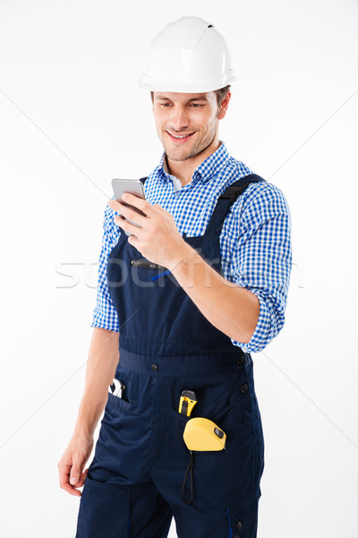Portrait of a handsome builder standing and using mobile phone Stock photo © deandrobot