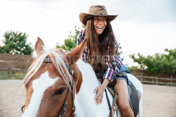 Smiling cute young womna cowgirl riding a horse outdoors Stock photo © deandrobot