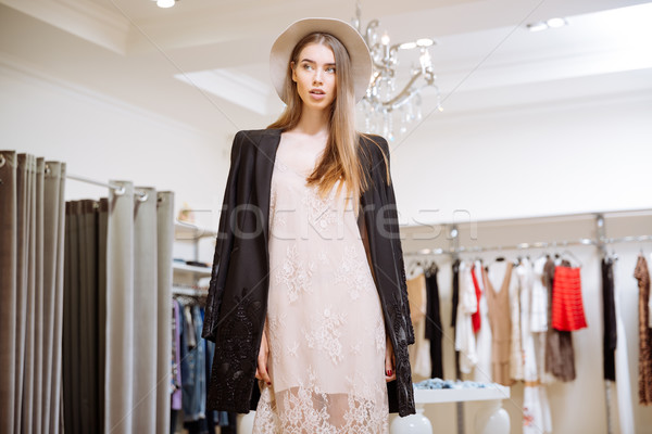 Gorgeous woman in dress, jacket and hat at clothig store Stock photo © deandrobot