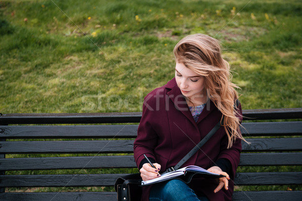 Thoughtful woman sitting on bench and writing in notebook outdoors Stock photo © deandrobot