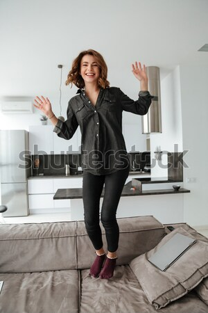 Tired asian businesswoman standing barefoot and holding high heels shoes Stock photo © deandrobot