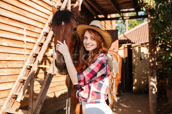 Happy woman cowgirl standing and hugging her horse Stock photo © deandrobot