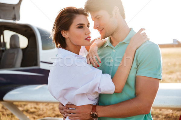 Couple standing and hugging near private aircraft Stock photo © deandrobot